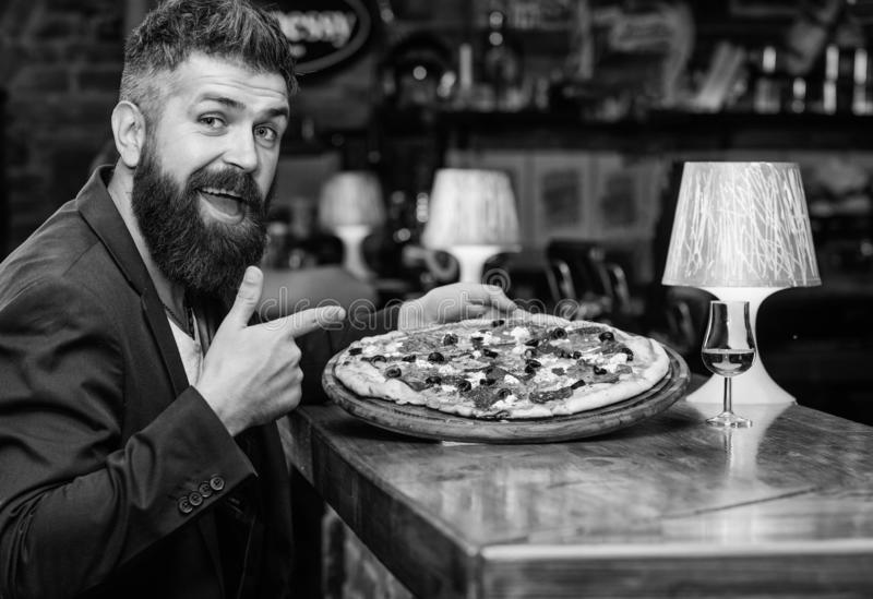 Hipster hungry eat italian pizza. Pizza favorite restaurant food. Fresh hot pizza for dinner. Hipster client sit at bar. Counter. Man received delicious pizza royalty free stock photos