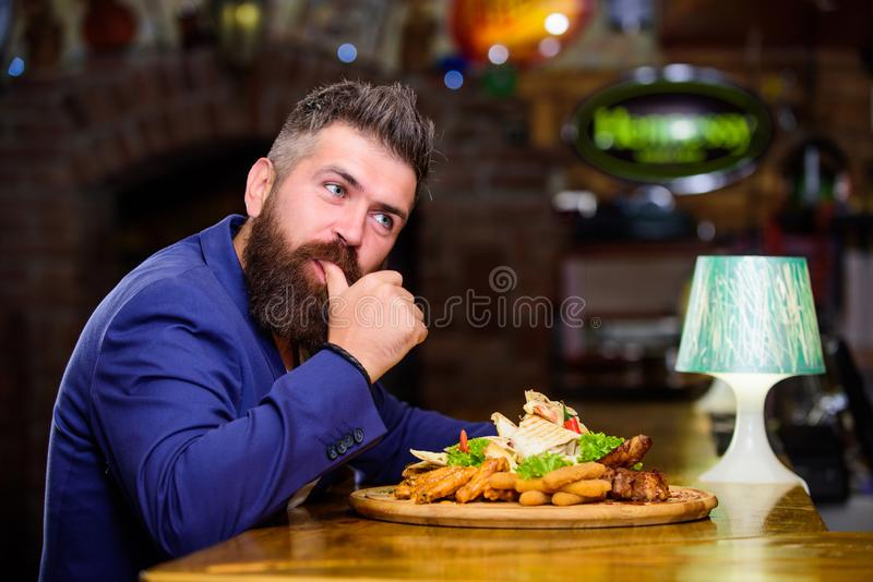 Hipster hungry eat pub fried food. Man received meal with fried potato fish sticks meat. High calorie snack. Enjoy meal. Cheat meal concept. Manager formal stock image