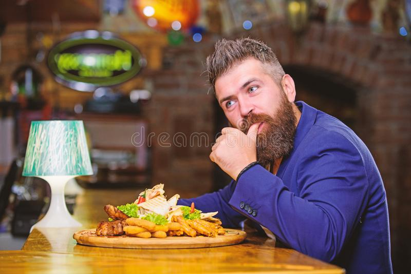 Hipster hungry eat pub fried food. Man received meal with fried potato fish sticks meat. High calorie snack. Enjoy meal. Cheat meal concept. Manager formal stock images
