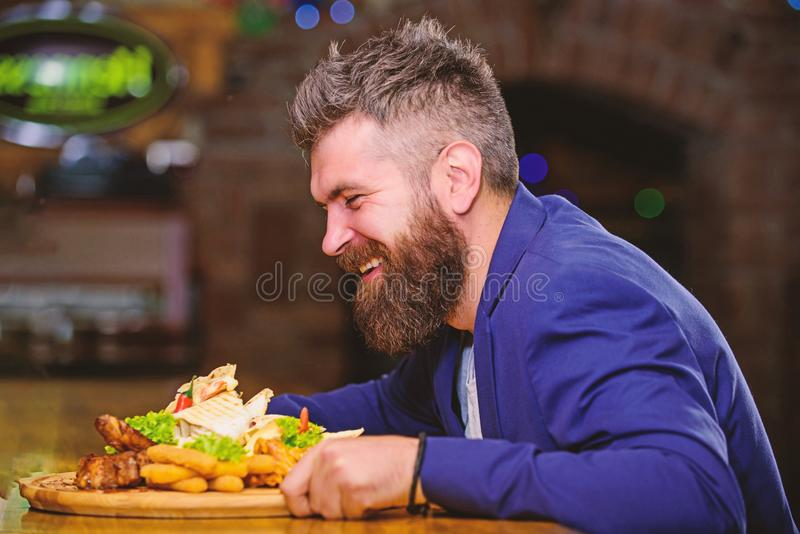 Hipster hungry eat pub fried food. Manager formal suit sit at bar counter. Delicious meal. Man received meal with fried. Potato fish sticks meat. High calorie stock photo