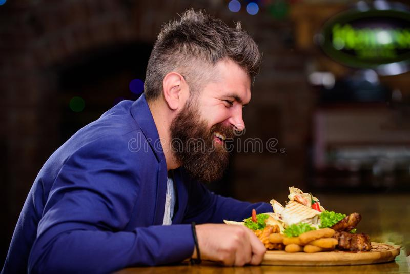 Hipster hungry eat pub fried food. Manager formal suit sit at bar counter. Delicious meal. Man received meal with fried. Potato fish sticks meat. High calorie royalty free stock images