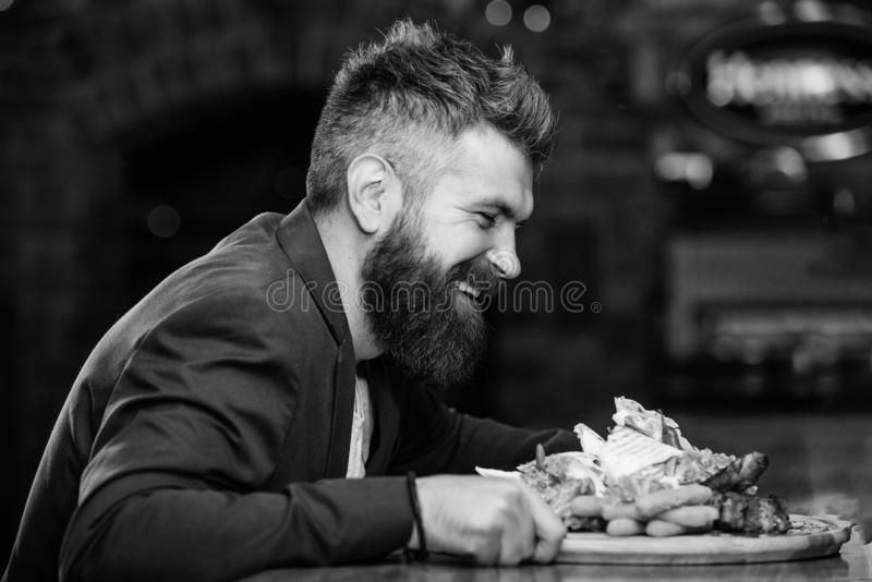 Hipster hungry eat pub fried food. Manager formal suit sit at bar counter. Delicious meal. Man received meal with fried. Potato fish sticks meat. High calorie royalty free stock image