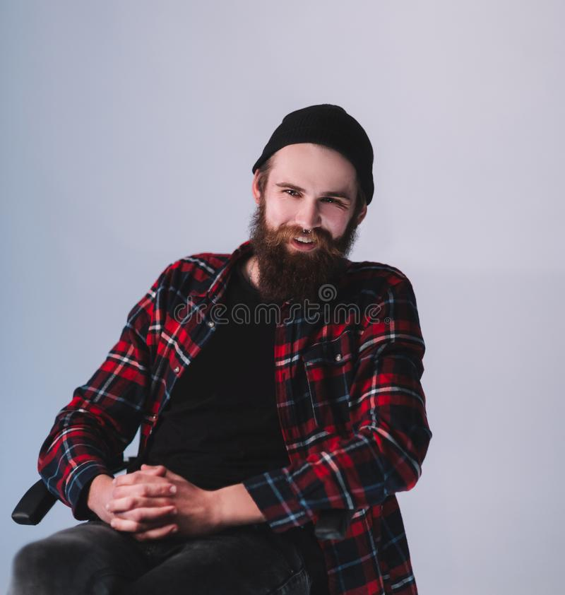 Hipster in jeans and plaid shirt sitting in a chair. Photo with copy space stock image