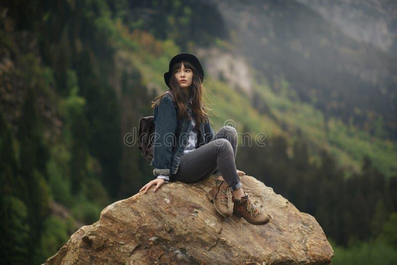 Hipster jong meisje die met rugzak van zonsondergang op piekberg genieten Toeristenreiziger op de mening van het achtergrondvalle stock foto