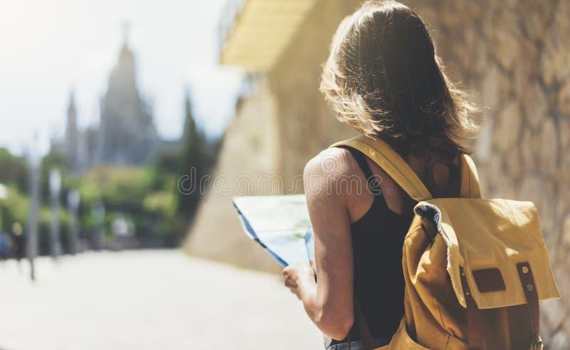 Hipster jong meisje met rugzak gebruikend en bekijkend kaart De bovengenoemde reiziger die van de meningstoerist op achtergrond v royalty-vrije stock afbeelding
