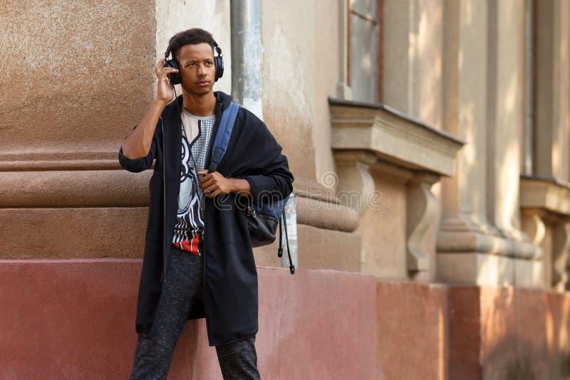 Hipster jonge kerel het luisteren muziek in zijn hoofdtelefoons, in straat, beeld met exemplaarruimte stock afbeelding