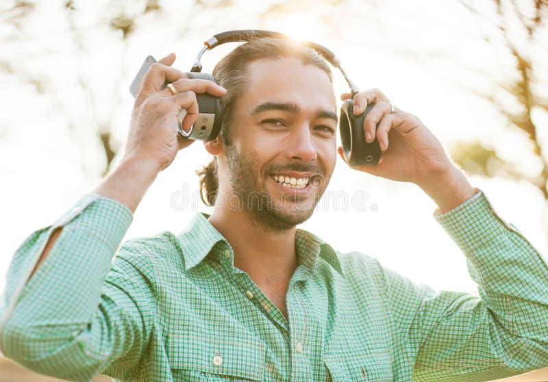 Hipster jonge mens die aan muziek luisteren stock foto's