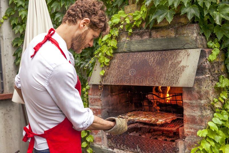 Hipster jonge mens die een barbecuepartij voorbereiden stock foto