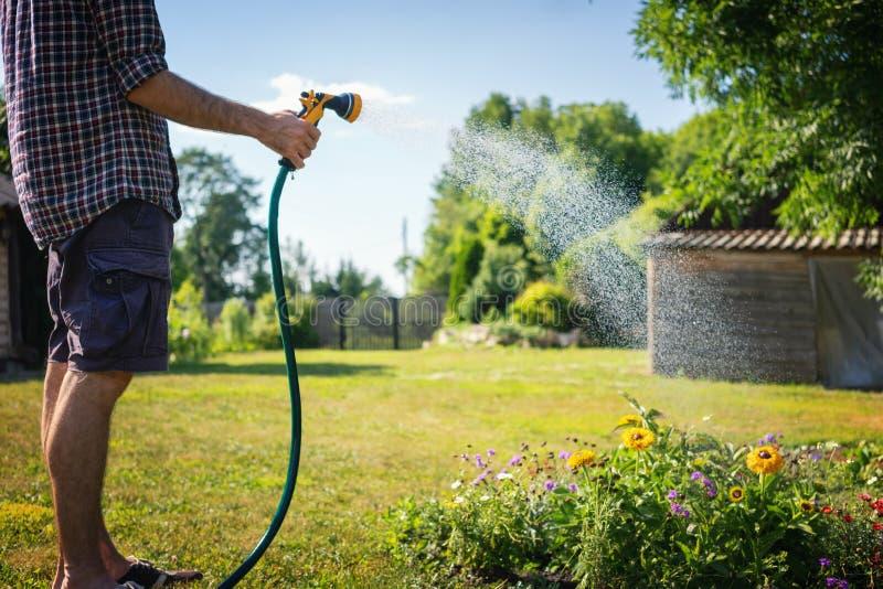 Hipster jonge mens het water geven installaties in een buitenhuis, de zomer en een tuinzorg stock afbeeldingen
