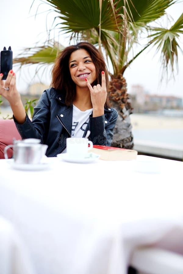 Hipster jonge vrouw die een beeld van zich op haar celtelefoon nemen die speels kijken stock foto's