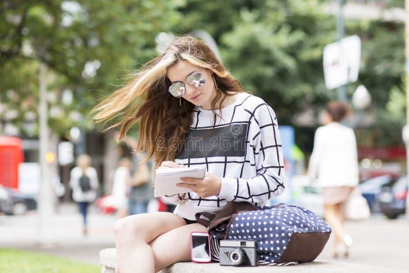 Hipster jonge vrouw die en nota's in stret reizen nemen stock foto's
