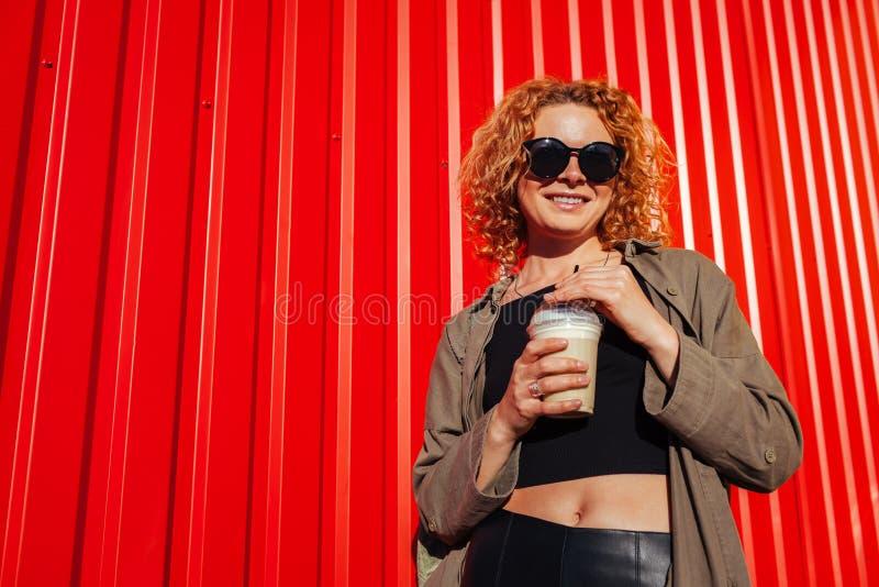 Hipster jonge vrouw met krullende rode haar het drinken koffie tegen rode muur Modieus de zomermeisje in zonnebril het glimlachen stock afbeeldingen