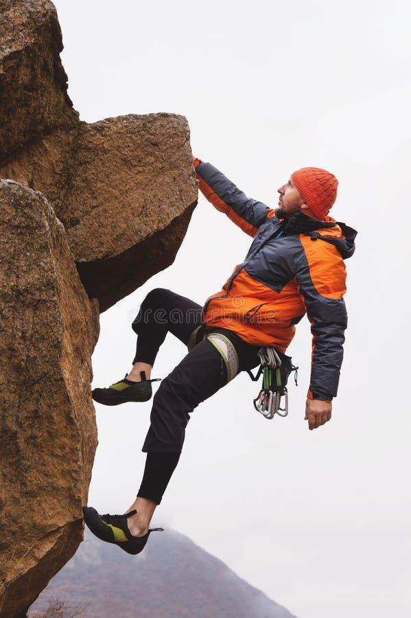 Hipster - klättrare som hänger på en hand på en vagga mot bakgrunden av de Caucasian bergen i sen höst arkivbilder