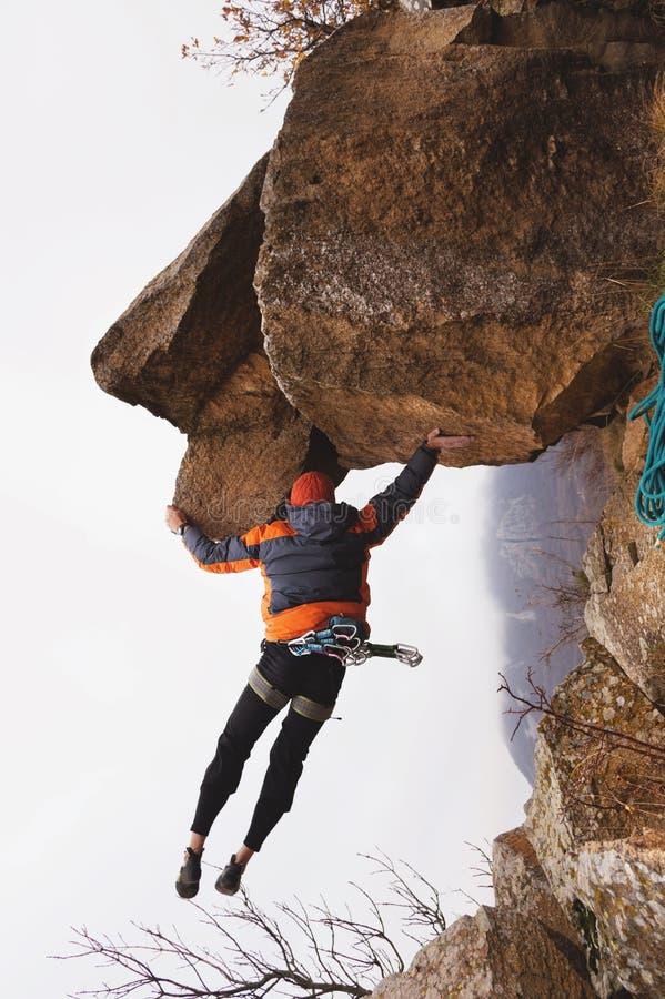 Hipster - klimmer het hangen op één hand op een rots tegen de achtergrond van de Kaukasische bergen in de recente herfst stock afbeelding