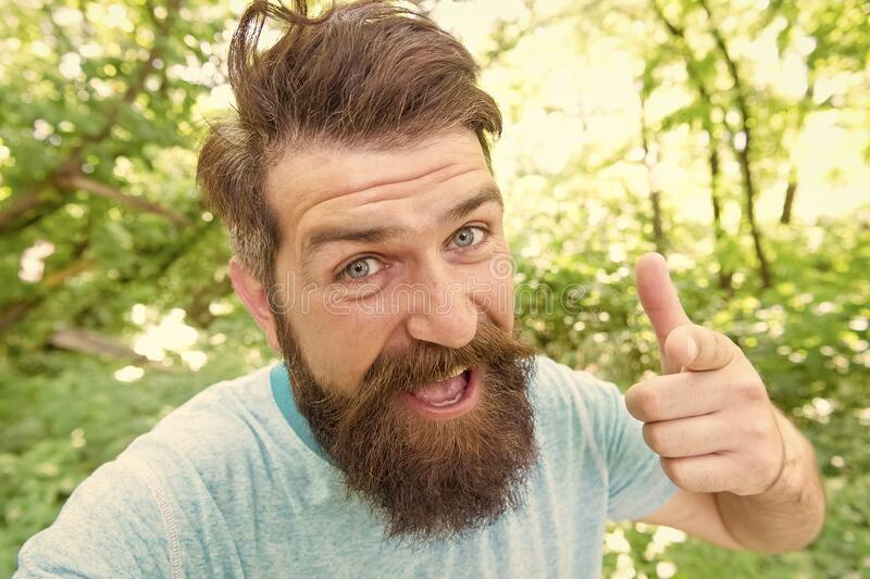 Hipster with long beard emotional face close up nature background. Summer fun. Bearded guy in park forest. Bearded stock photo
