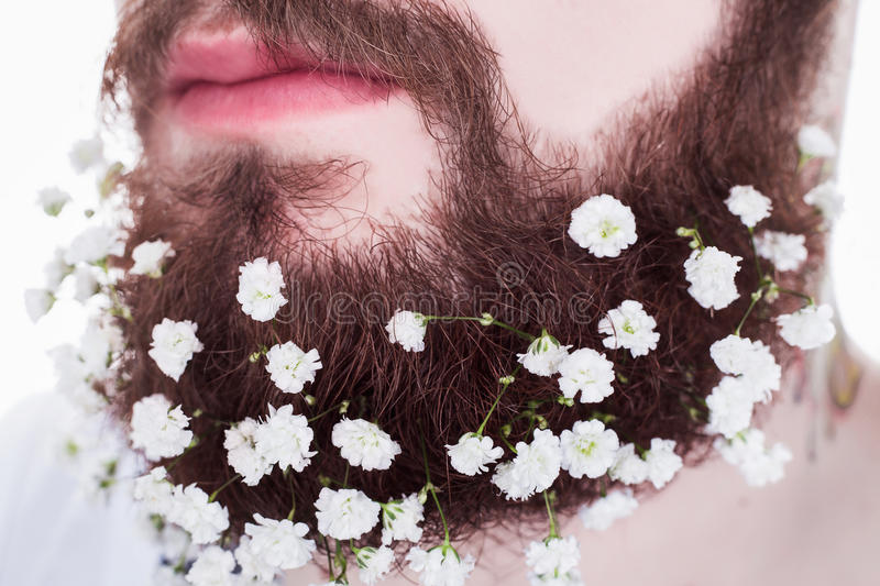 Hipster with long beard and flowers stock image