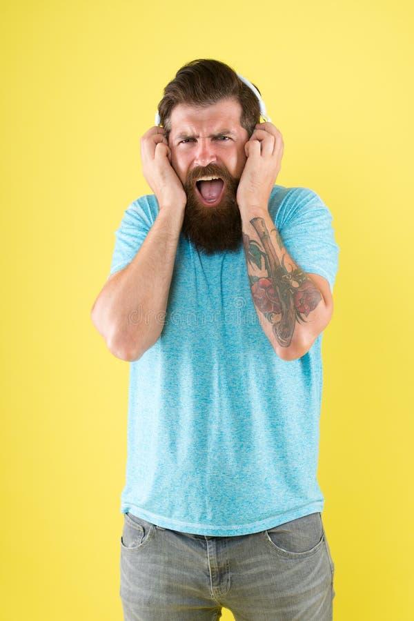 Hipster luistert het gebroken gadget van de hoofdtelefoonsmuziek Verachtelijk lied muzieksmaak De gebaarde muziek van de kerelafk royalty-vrije stock afbeelding