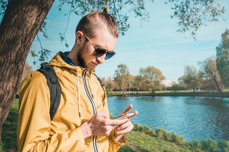 Hipster male touch mobile phone outdoor summer lifestyle in park. Outdoor summer lifestyle portrait of young bearded man using white smartphone in summer park royalty free stock image