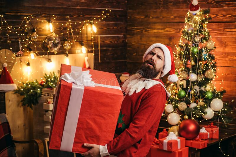 Hipster man, bearded Santa celebrate Thanksgiving day and Christmas. Santa man holding gift. Delivery gifts. Gift stock photo
