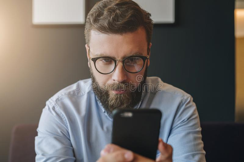 Hipster man is chatting, blogging, checking email. Student learning online.Online marketing, education. Portrait of young bearded attractive businessman in royalty free stock images