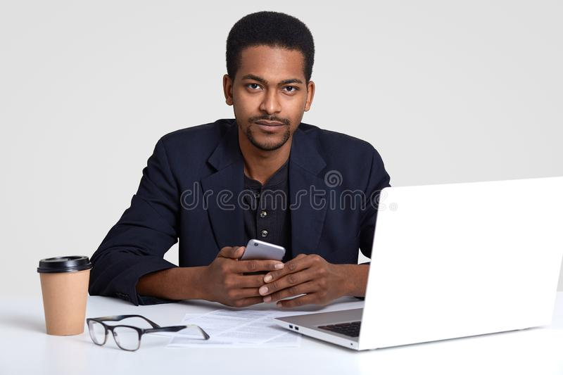 Hipster man with dark skin, wears elegant suit, sits at workplace, uses modern technologies, holds smart phone, recieves royalty free stock photo