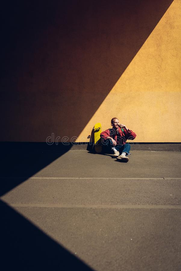 Hipster man drinking coffee sitting on ground. Urban lifestyle and activity. Full length portrait of young red haired hipster guy sitting on ground of road stock image