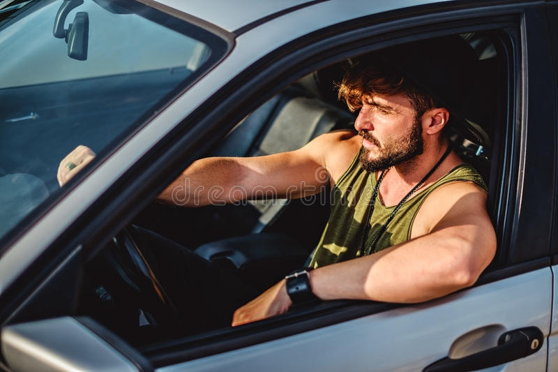 Hipster man driving a car on a sunny day royalty free stock photography