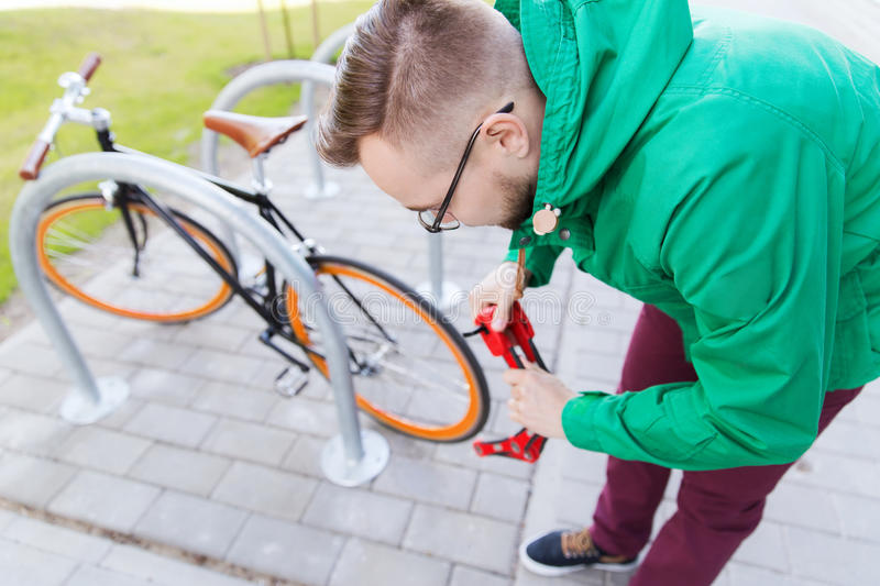 Hipster man fastening fixed gear bike with lock stock images