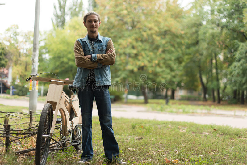 Hipster man with his cruiser wooden handmade bike. Hipster man with his cruiser wooden handmade bicycle stock images