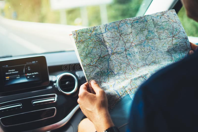 Hipster man looking and point finger on location navigation map in car, tourist traveler driving and hold in male hands europe car royalty free stock image