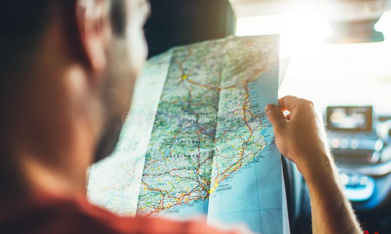 Hipster man looking and point finger on location navigation map in car, tourist traveler driving and hold in male hands europe car. Tography, view and plan royalty free stock photos