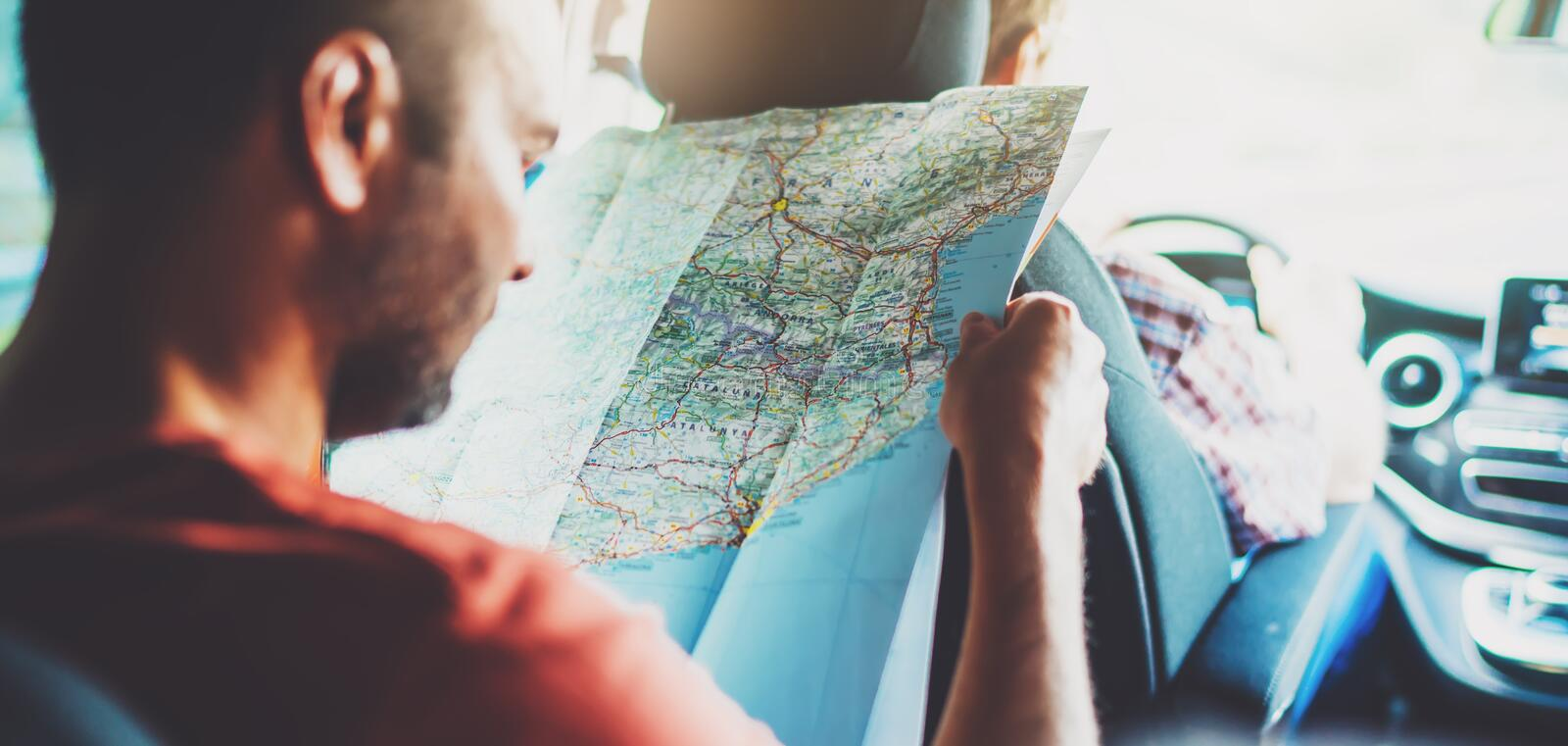 Hipster man looking and point finger on location navigation map in car, tourist traveler driving and hold in male hands europe car stock photo