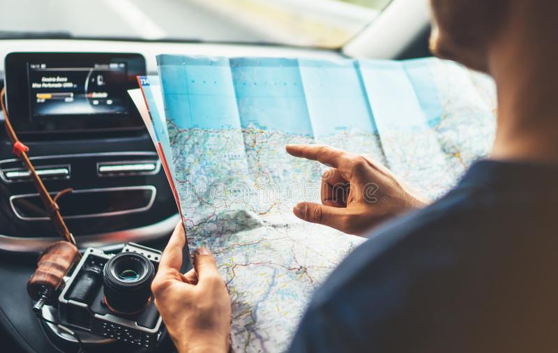 Hipster man looking and point finger on location navigation map in car, tourist traveler driving and hold in male hands europe car stock image