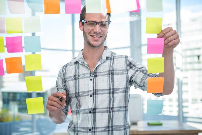 Hipster man looking at post-it stock photos