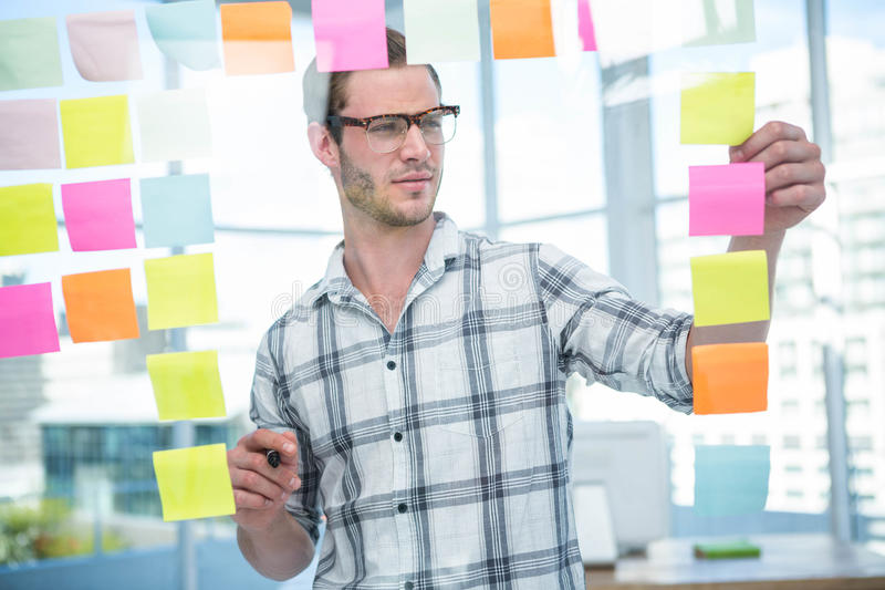 Hipster man looking at post-it royalty free stock photography