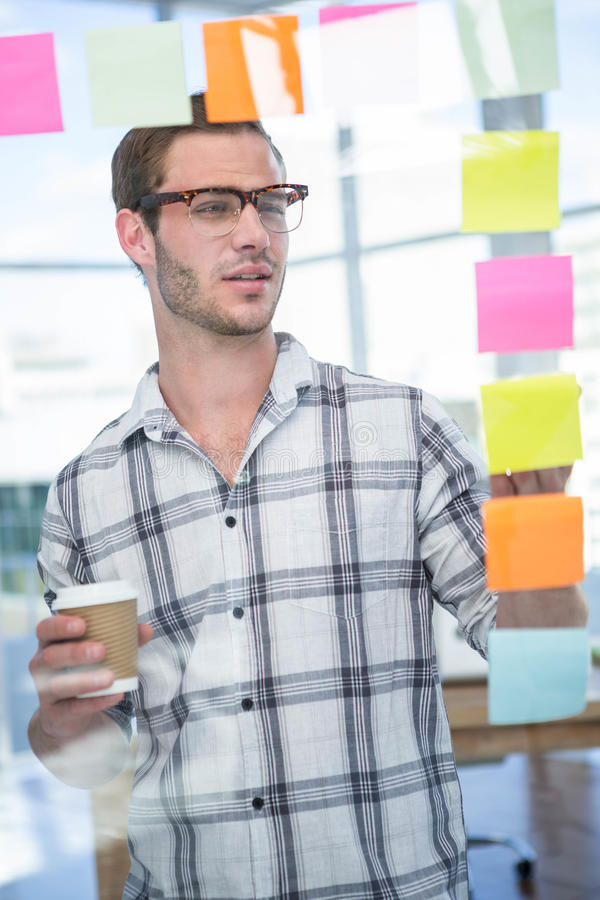 Hipster man looking at post-it stock photography