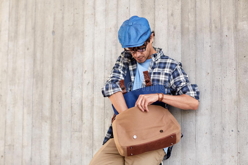 Hipster Man Looking For Something In His Bag Stock Photo