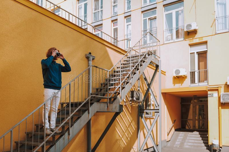Hipster man making photo on camera on stairs. Urban lifestyle concept. Full length portrait of young red haired hipster guy making photo on camera while staying stock images