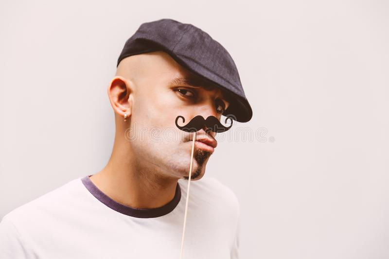 Hipster man with paper mustache making fanny face stock photos