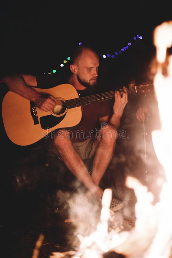 Hipster man playing on acoustic guitar and singing song at big bonfire at camp, chilling with friends in the forest. Group of stock photo