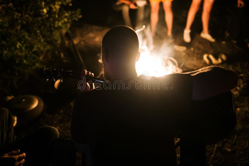 Hipster man playing on acoustic guitar and singing song at big bonfire at camp, chilling with friends in the forest. Group of stock photos