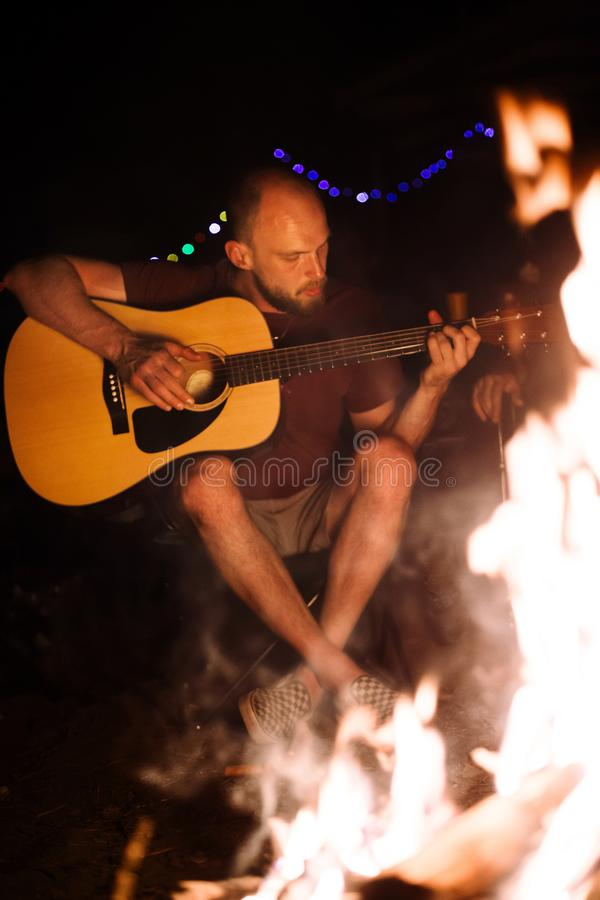 Hipster man playing on acoustic guitar and singing song with friends travelers at big bonfire at night camp in the forest. Group royalty free stock image