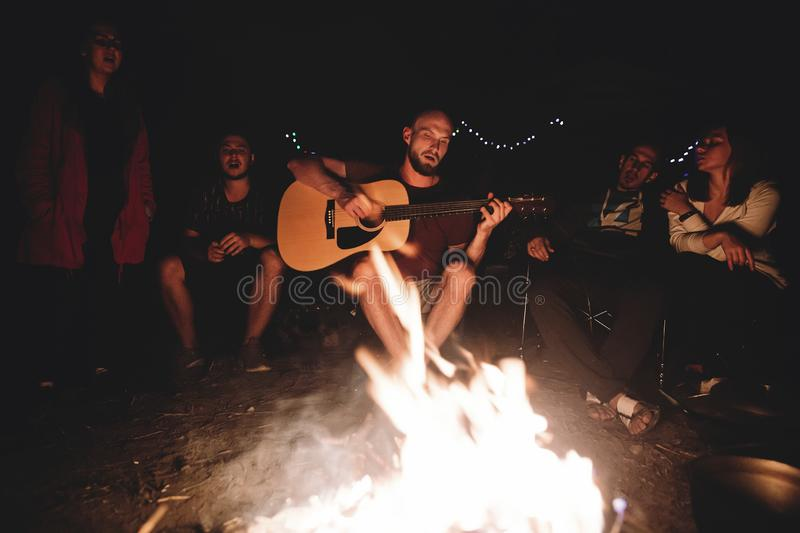 Hipster man playing on acoustic guitar and singing song with friends travelers at big bonfire at night camp in the forest. Group stock photography
