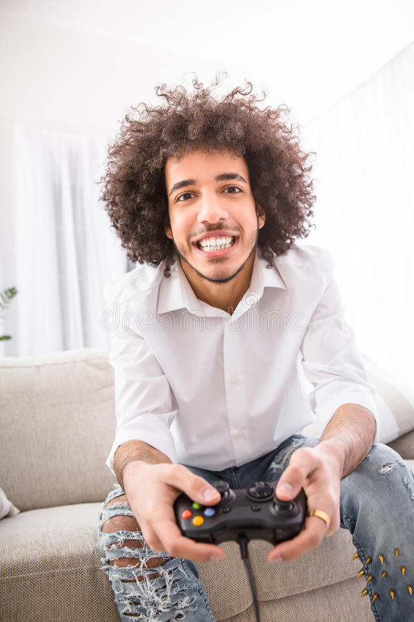 Hipster man playing computer games stock image