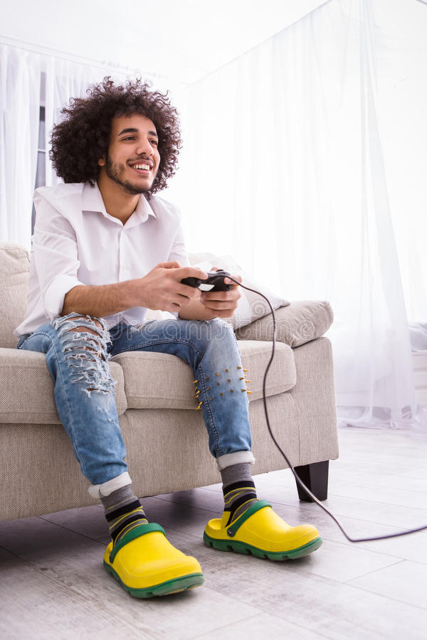 Hipster man playing computer games stock photo