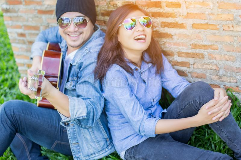 Hipster man playing guitar for his girlfriend outdoor against brick wall, enjoying together. Hipster men playing guitar for his girlfriend outdoor against brick royalty free stock photos