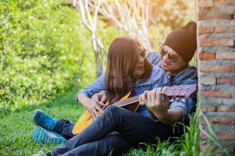Hipster man playing guitar for his girlfriend outdoor against brick wall, enjoying together. Hipster men playing guitar for his girlfriend outdoor against brick stock images