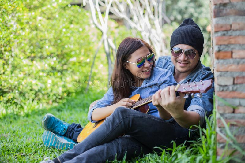 Hipster man playing guitar for his girlfriend outdoor against brick wall, enjoying together. Hipster men playing guitar for his girlfriend outdoor against brick stock photo