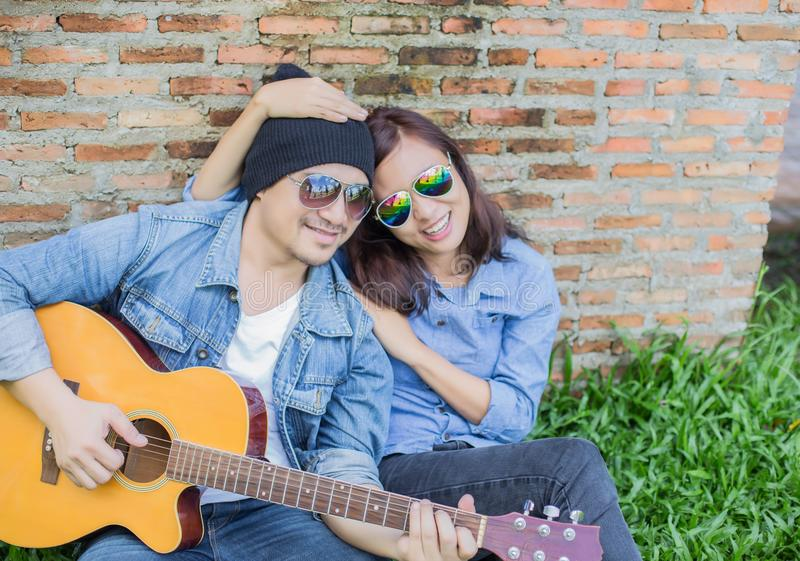 Hipster man playing guitar for his girlfriend outdoor against brick wall, enjoying together. Hipster men playing guitar for his girlfriend outdoor against brick stock image