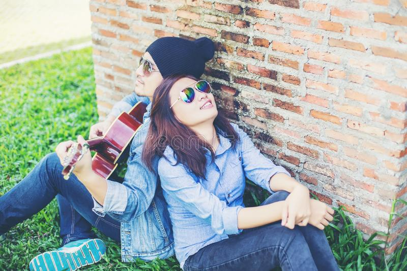 Hipster man playing guitar for his girlfriend outdoor against brick wall, enjoying together. Hipster men playing guitar for his girlfriend outdoor against brick royalty free stock photography